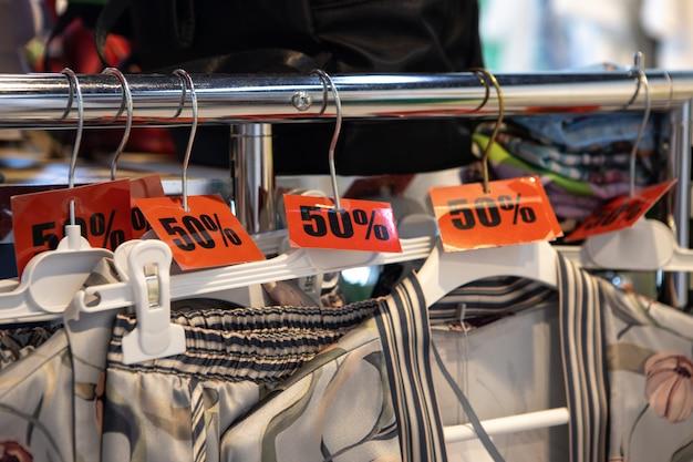캐주얼 또는 가정 의류 매장의 옷걸이에 50% 할인 판매 태그 할인. 패션 컨셉, 할인 시즌, 블랙 프라이데이, 오프라인 쇼핑, 특수 효과, 휴일 판매, 잠옷. 측면보기.