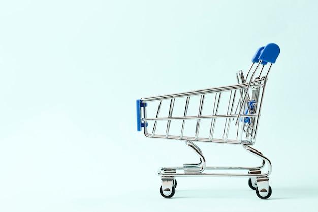 割引の概念。テキスト用のスペースと青い背景のショッピングカート