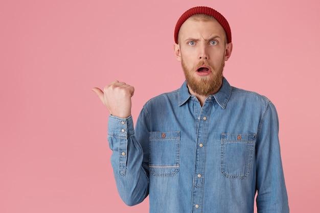 Обескураженный изумленный мужчина, удивленно открыл рот и показывает большим пальцем влево на копировальной площади, парень в красной шляпе с рыжей густой бородой, носит джинсовую рубашку, изолирован
