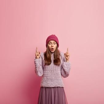 Donna scoraggiata e impressionata in copricapo, apre la bocca per la sorpresa, punta le dita verso l'alto, attira la tua attenzione sullo spazio della copia, prova paura, isolata su un muro rosa. concetto di promozione