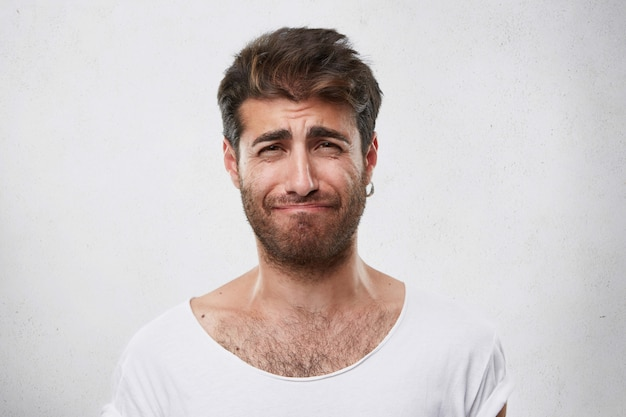 髪型とあごひげが顔をしかめ、落胆してしまったことを気の毒に思った男。白いtシャツを着た悲嘆の男。人、ファッション、ライフスタイル、感情の概念
