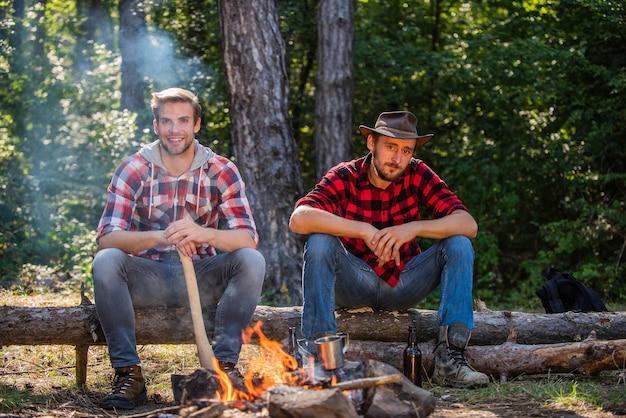 Откройте для себя концептуальный поход life adventure, и люди, двое мужчин, отдыхают в походах по костру и в кемпинге.