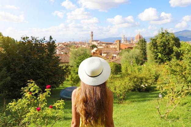 Знакомство с флоренцией. вид сзади молодой туристической девушки, глядя на городской пейзаж флоренции между деревьями в парке. туризм в тоскане.