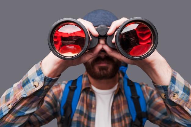 새로운 장소를 발견합니다. 회색 배경에 서 있는 동안 배낭을 메고 쌍안경을 통해 바라보는 자신감 있는 수염 난 남자