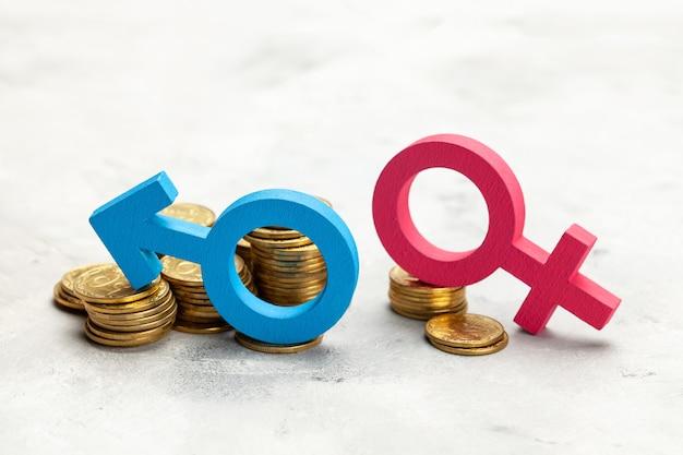 여성 차별. 동전의 큰 스택과 남자의 성별 기호와 동전의 작은 스택과 여자의 성별 기호. 급여 차별.