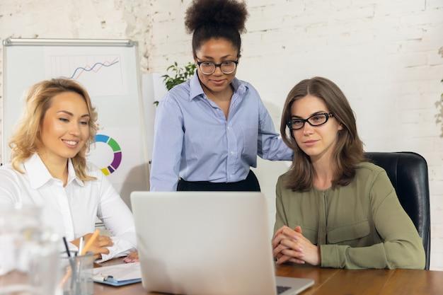 논의하다. 창의적인 회의 중에 장치와 가제트를 사용하여 현대적인 사무실에서 함께 일하는 동료.