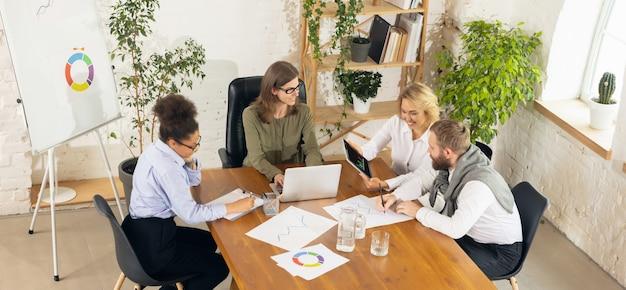 Обсуждать. коллеги работают вместе в современном офисе с помощью устройств и гаджетов во время творческой встречи.
