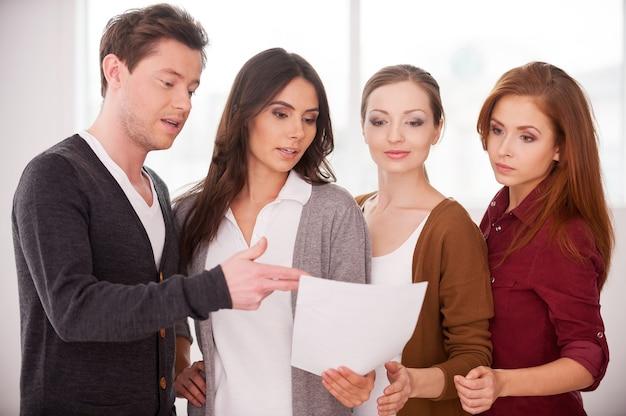 Обсуждаем контракт. группа молодых людей обсуждает документ, стоя рядом друг с другом