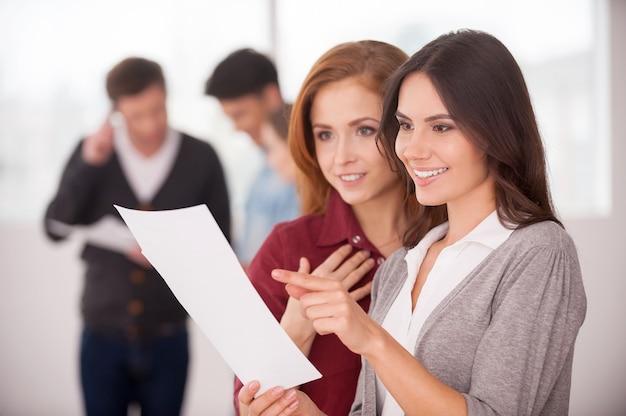 Обсуждение контракта в хорошем состоянии. две красивые молодые женщины обсуждают документ, пока двое мужчин общаются на заднем плане