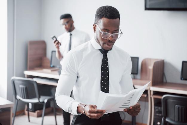 プロジェクトについて議論します。正装で2人の黒人ビジネスマンが紙を指差しながら何かを話し合っている