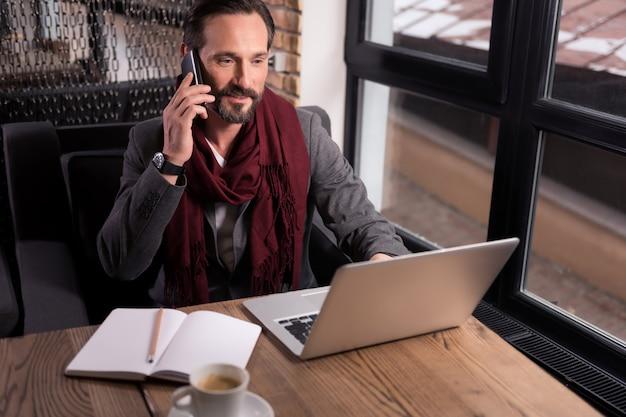 비즈니스 문제에 대해 논의합니다. 노트북 앞에 앉아 작업하는 동안 전화 대화를 나누는 잘 생긴 즐거운 자신감 사업가