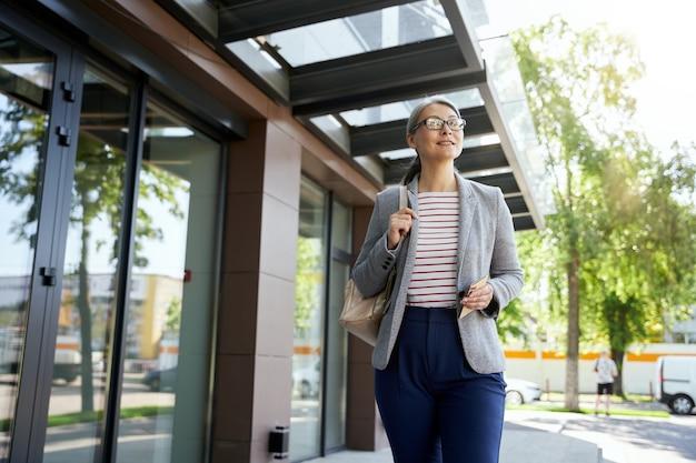 사업에 대해 논의 중입니다. 스마트폰을 사용하여 무선 이어폰을 착용하고 야외에 서 있는 동안 전화로 누군가와 이야기하는 아름답고 행복한 여성의 초상화. 비즈니스 사람, 작업
