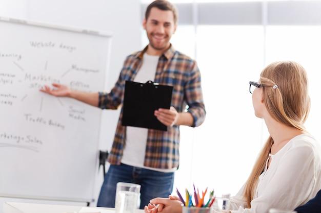 Обсуждаем бизнес-стратегию. уверенный молодой человек в элегантной повседневной одежде, стоящий возле доски и указывая на нее с улыбкой, пока женщина сидит на переднем плане