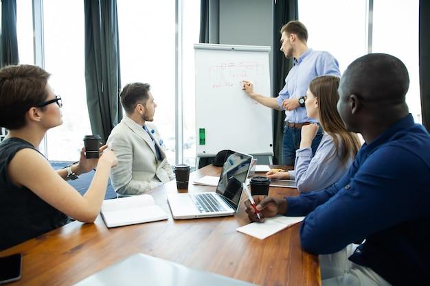 회사 진행 상황에 대해 논의합니다. 화이트 보드 근처에 서서 그의 동료가 책상에 앉아있는 동안 그래프를 가리키는 확신 젊은 남자.