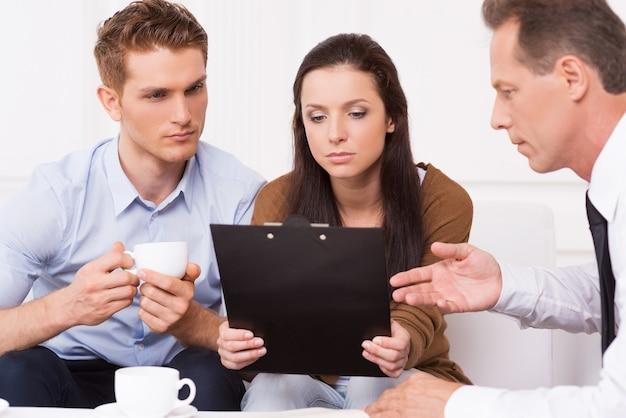 Обсуждение условий контракта. задумчивая молодая пара сидит на диване, пока зрелый мужчина в строгой одежде что-то объясняет и указывает на буфер обмена