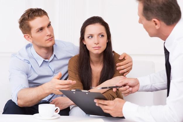 Обсуждаем контракт. задумчивая молодая пара сидит на диване, пока мужчина в строгой одежде что-то объясняет и указывает на буфер обмена