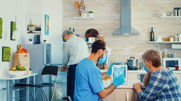 엑스레이를 보고 가정 방문 중에 노인 환자와 진단에 대해 논의합니다. 질병 예방을 위한 남자 간호사의 노인 의료 방사선 사진, 은퇴한 노인 여성을 검사합니다.