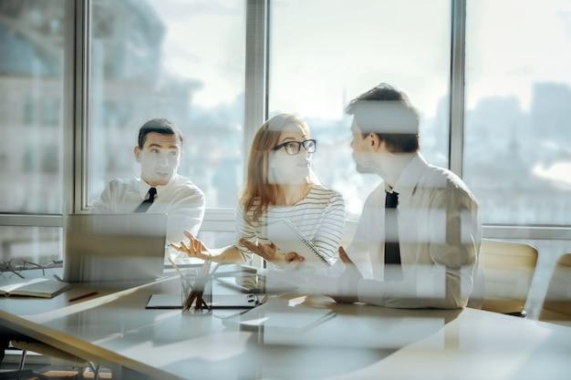 熱心に話し合う。魅力的な若い女性と2人の男性の同僚がテーブルに座って、白熱した議論をしています