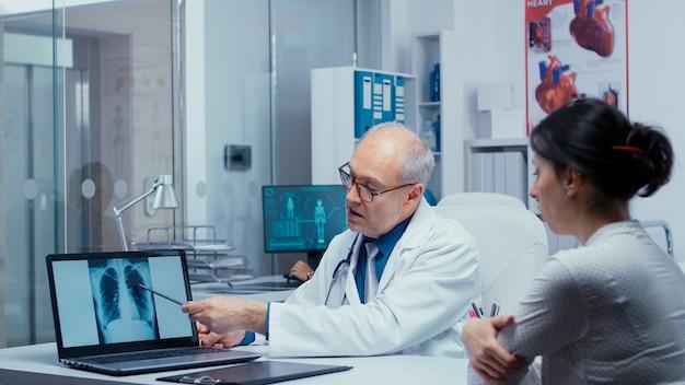 若い女性患者と肺x線の結果について話し合う。肺、x線肺炎、癌、modで診断をコンサルティングする検査スペシャリストについて患者と話している高齢の経験豊富な医師