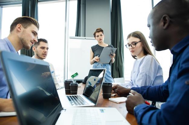 新しいビジネスアイデアについて話し合う。ホワイトボードの近くに立って、同僚が机に座っている間笑顔の陽気な若い女性。