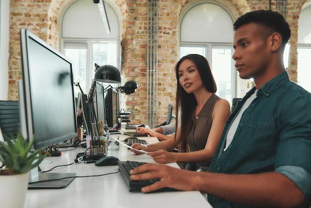 Обсуждая новую бизнес-стратегию, двое молодых людей в повседневной одежде смотрят на монитор компьютера и