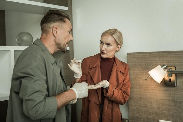 논의 대상. 동료에게 램프에 숨어있는 청취 장치를 보여주는 매력적인 전문 수사관
