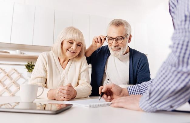 완벽한 집 레이아웃에 대해 논의합니다. 집의 레이아웃과 도면을 시연하면서 노년층 고객과 만나는 야심 찬 긍정적 인 숙련 된 부동산 중개인
