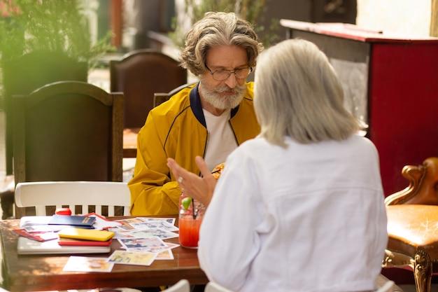 계획을 논의 중입니다. 여자는 거리 카페에서 남편과 함께 앉아 활발한 대화를 나누며 미친 듯이 몸짓을 하고 있습니다.