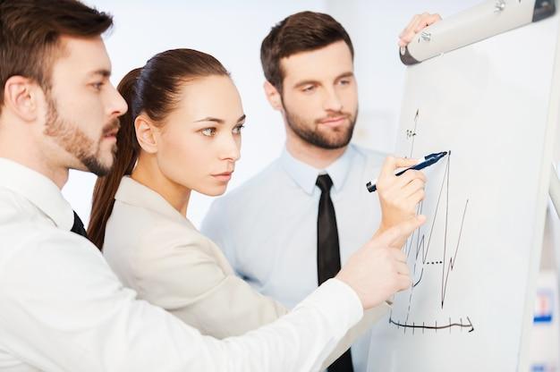 Обсуждаем график прогресса. трое уверенных в себе деловых людей обсуждают график на доске, стоя рядом друг с другом