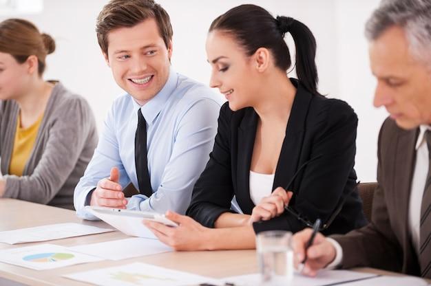Обсуждаем проект вместе. уверенные деловые люди сидят в ряд за столом, в то время как мужчина и женщина в формальной одежде разговаривают друг с другом и улыбаются