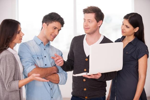 Обсуждаем проект вместе. группа молодых людей что-то обсуждает, пока один мужчина держит ноутбук