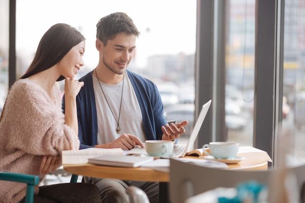 결과에 대해 논의합니다. 비즈니스 회의 중 작은 레스토랑에 앉아있는 동안 노트북에서 함께 일하는 젊은 사람들의 쌍.