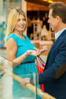 매각 논의 중. 쇼핑몰에 서있는 동안 서로 이야기하는 아름다운 성숙한 부부