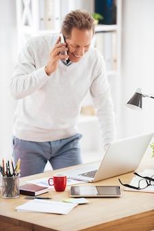 몇 가지 비즈니스 문제를 논의합니다. 쾌활한 성숙한 남자가 사무실 책상 근처에 서서 휴대전화로 통화하고 노트북을 보고 있다