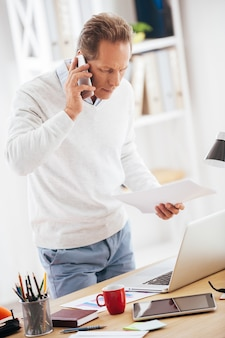Discussing some business issues. confident mature man talking on the mobile phone and looking at his laptop while standing near his desk in office