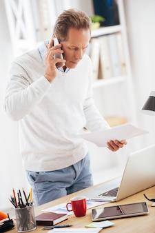 몇 가지 비즈니스 문제를 논의합니다. 사무실 책상 근처에 서서 휴대전화로 통화하고 노트북을 바라보는 자신감 있는 성숙한 남자