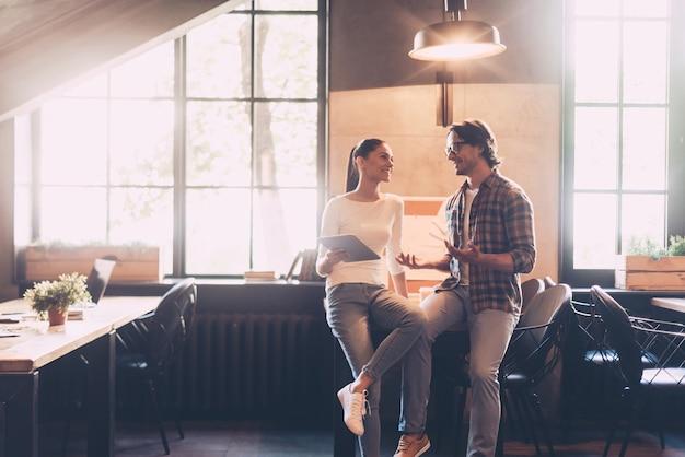 몇 가지 작업 문제에 대해 논의합니다. 쾌활한 젊은 남성과 여성이 창의적인 사무실에서 나무 책상에 기대어 무언가를 토론하고 웃고 있습니다.