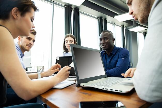Обсуждение успешного проекта. группа молодых веселых деловых людей, работающих и общающихся, сидя за офисным столом вместе с коллегами, сидящими на заднем плане.