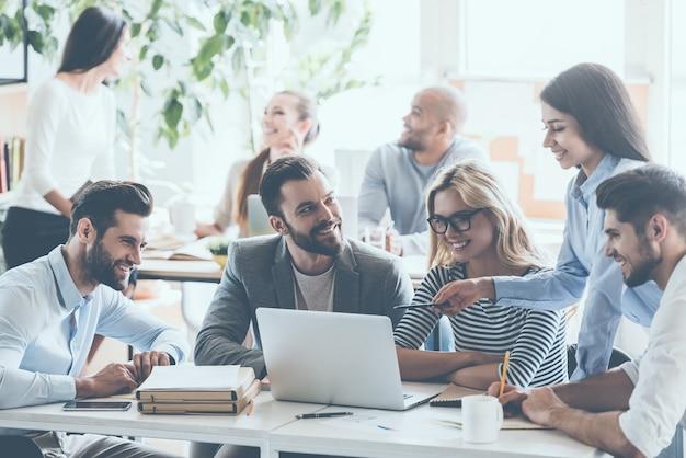 Обсуждение успешного проекта. группа молодых веселых деловых людей, работающих и общающихся, сидя за офисным столом вместе с коллегами, сидящими на заднем плане