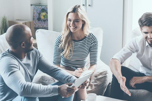 Обсуждение успешного проекта. молодые деловые люди что-то обсуждают и улыбаются, сидя на стульях в офисе