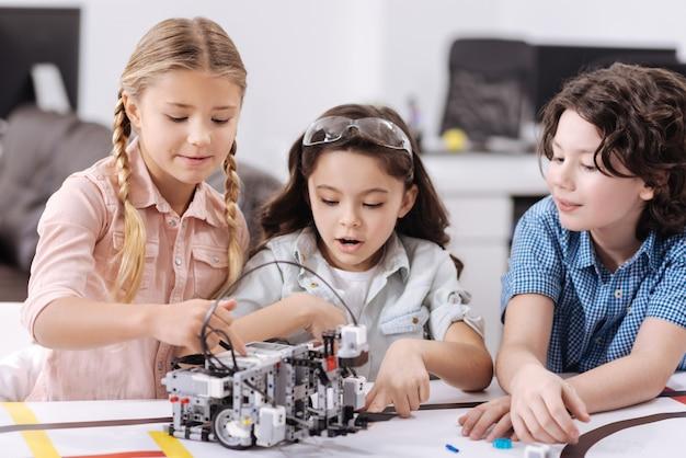 技術研究について話し合う。学校に座って、ロボットを構築しながら技術クラスを楽しんでいる陽気なアクティブな小さな科学者