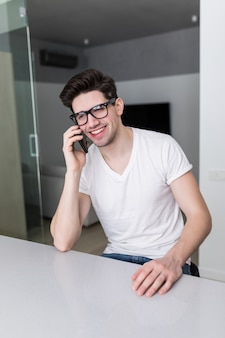 Обсуждая этот документ. серьезный человек держит бумагу и разговаривает по мобильному телефону, сидя дома