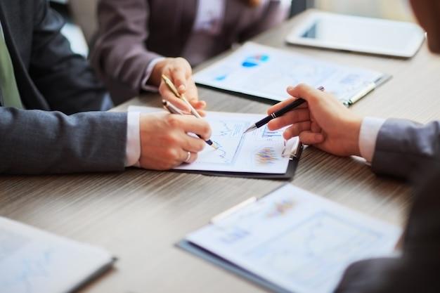 계획에 대해 논의합니다. 비즈니스 사람들의 측면보기, 테이블에 앉아 함께 차트에 핸들을 가리키는