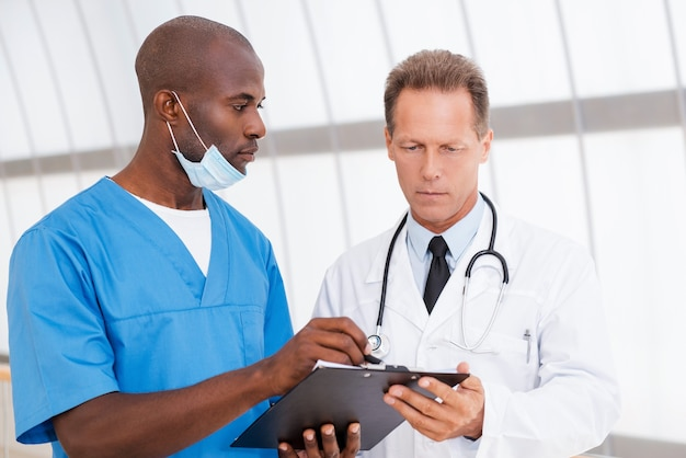 治療について話し合う。 2人の自信のある医師が何かについて話し合い、そのうちの1人がクリップボードを指しています