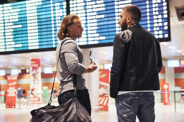 Discussion about planning a trip. photo of two comrades situating in airport near flight information display system