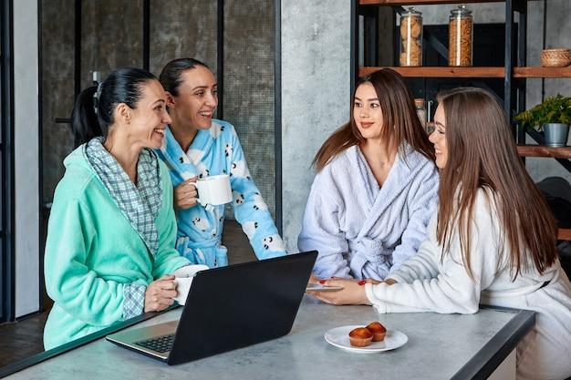 아침 식사에서 가족 축하에 대한 토론 드레싱 가운을 입은 4명의 여성이 식탁에서 즐겁게 수다