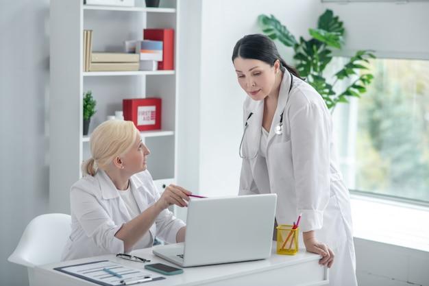 Обсуждение. две женщины-врачи в белых халатах обсуждают дело