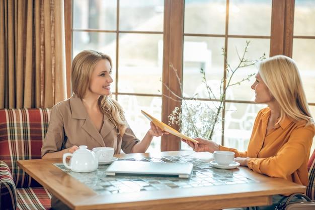 討論。カフェのテーブルに座って話したり話し合ったりする2人の女性