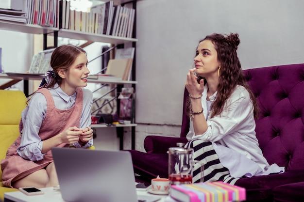 友達と話し合う。好奇心旺盛な親友に物語を語る白いシャツを着た思いやりのある黒髪の少女