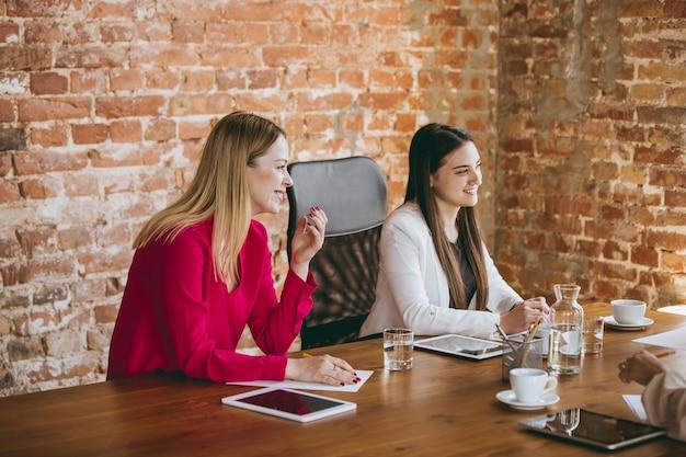 Обсуждение. молодая деловая женщина в современном офисе с командой. творческая встреча, постановка задач. женщины во фронт-офисе работают. понятие финансов, бизнеса, женской силы, включения, разнообразия, феминизма.